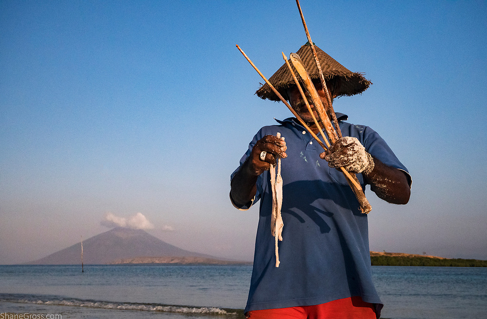 An Artisanal fisherman in a remote part of Indonesia collects worms to be used as fishing bait.