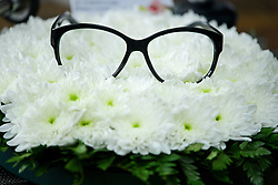 """© Licensed to London News Pictures. 18/04/2016. Shirley, UK.  Ronnie Corbett's glasses resting on flowers next to a note which reads """" .... AND IT""""S GOODNIGHT FROM HIM"""" at the funeral of comedian, actor, writer Ronnie Corbett at St John the Evangelist Church in Shirley near Croydon. Corbett, who was most famous for his comedy sketch show  The Two Ronnies, performed with the late Ronnie Barker, died at the age of 85. Photo credit: Ben Cawthra/LNP"""