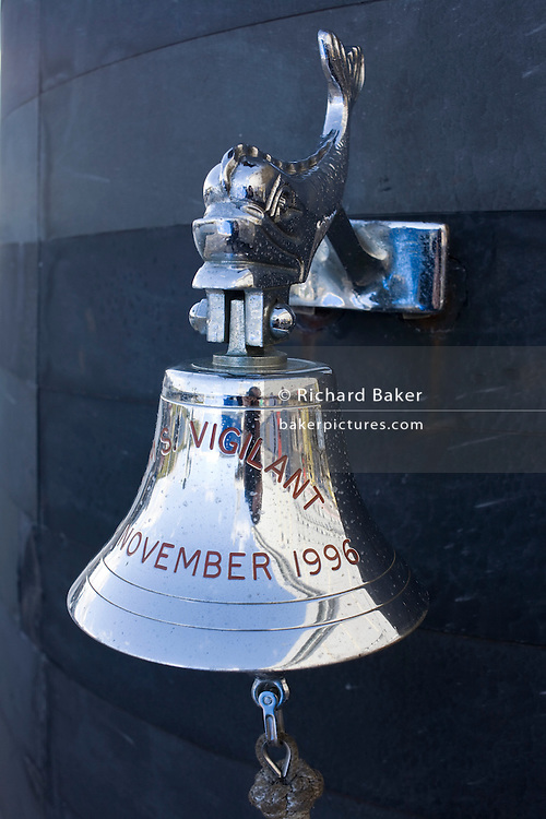 Silver Royal Navy ship's bell of HMS Vigilant, a Vanguard class nuclear submarine while docked at HM Naval Base Clyde, Faslane