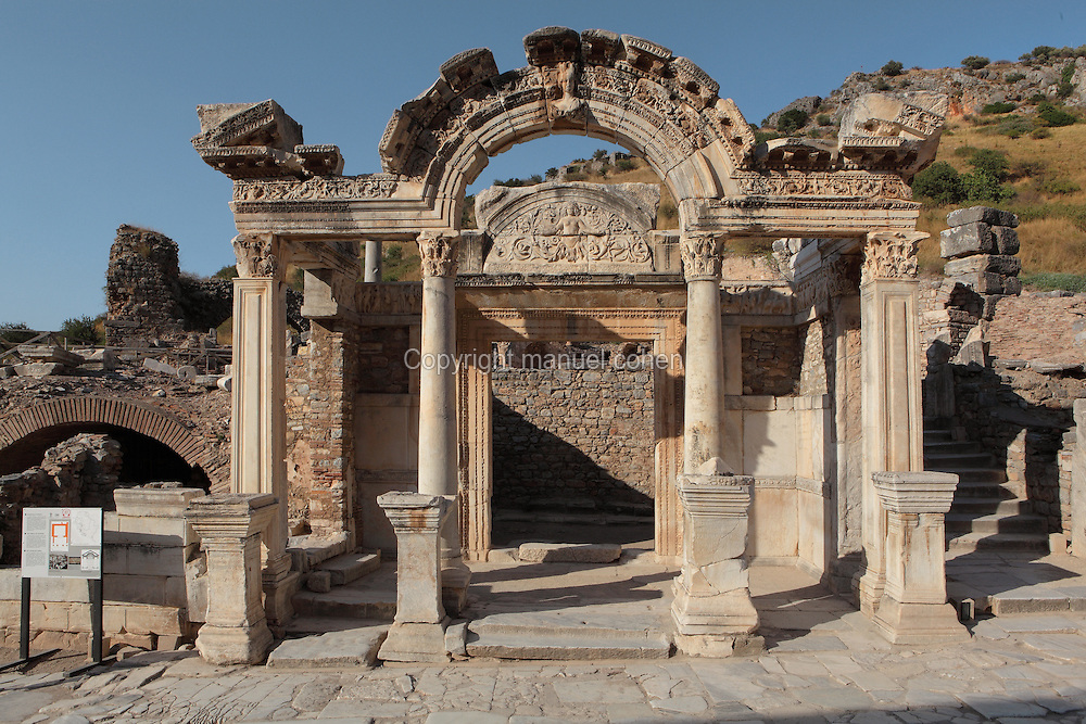Temple of Hadrian, 2nd century AD, Curetes Street, Ephesus, Izmir, Turkey. The temple was built by Quintilius before 138 AD and was dedicated to the Emperor Hadrian, who came to visit the city from Athens in 128 AD. The colonnade in front of the cella supports a so-called Syrian gable. The reliefs over the door lintel depicting the Ephesian foundation myth were added later. Around 300 AD statues of the emperors Diocletian, Constantius, Maximianus and later Theodosius I were erected, of which inscribed bases are preserved. The facade of the temple has 4 Corinthian style columns supporting a curved arch, in the middle of which contains a relief of Tyche, goddess of victory. The side columns are square. The pedestal with inscriptions in front of the temple, are the bases for the statues of emperors Diocletian, Maximian, Constantius I, and Galerius; the originals of the statues have not been found yet. Inside the temple above the door, a human figure, probably Medusa, stands with ornaments of acanthus leaves. Ephesus was an ancient Greek city founded in the 10th century BC, and later a major Roman city, on the Ionian coast near present day Selcuk. Picture by Manuel Cohen
