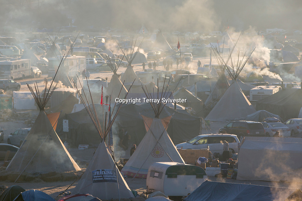 Smoke and mist catch the morning light in the opposition camp against the Dakota Access oil pipeline on November 25, 2016. Cannon Ball, North Dakota, United States.