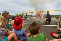 Erilyn Searles (wearing junior firefighter hat) can feel the heat as Dion DeCarli of Gilford Fire and Rescue conducts a demonstration on how quickly the shed engulfs in flames without an installed sprinkler system in the Lowe's Gilford parking lot on Saturday.    (Karen Bobotas/for the Laconia Daily Sun)