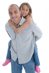 Portrait of a father giving his daughter a piggyback ride in the studio,