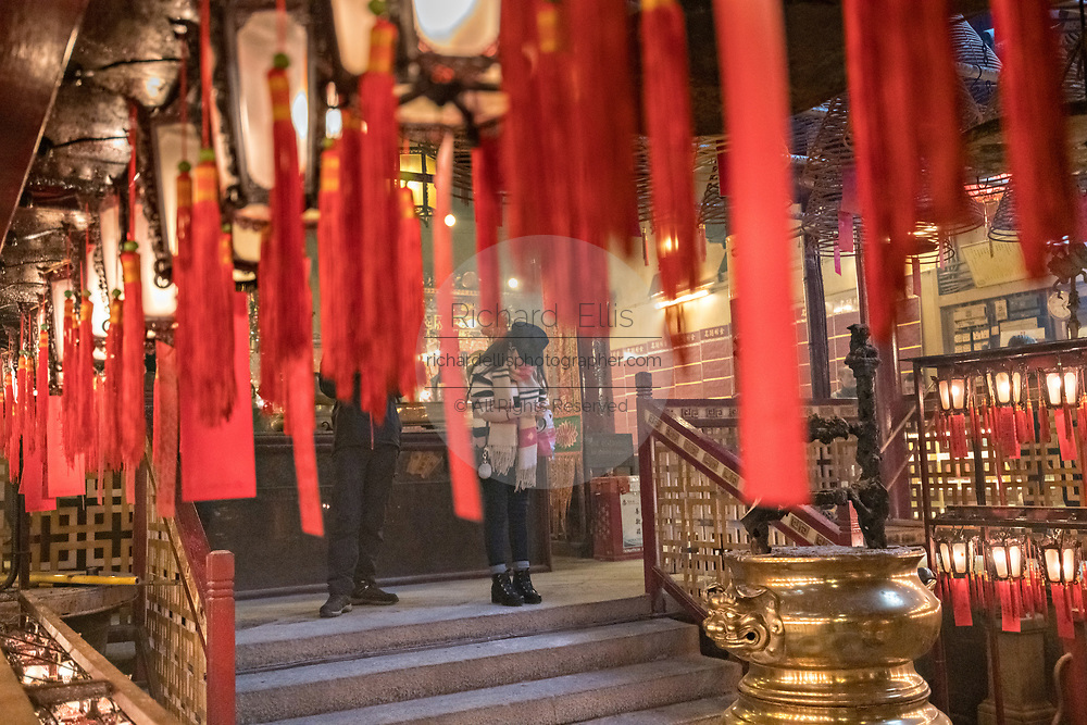 A worshipper presents an offering inside the Man Mo Temple which is dedicated to the God of Literature and the God of War and was built in 1847 in Sheung Wan District of Hong Kong Island. The Taoist temple is the largest Man Mo Temple in Hong Kong and includes two additional temples for Buddhist and Taoist deities.