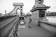 A young woman uses a skateboard to cross the Chain Bridge over the Danube River, going from the Pest to the Buda side, in Budapest, Hungary.