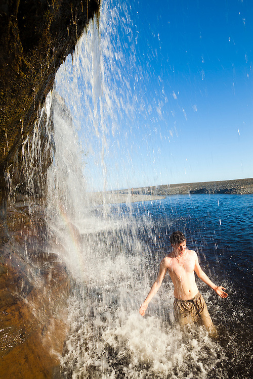 Zach Podell-Eberhardt throws himself under the spray of Tsusiat Falls, West Coast Trail, British Columbia, Canada.