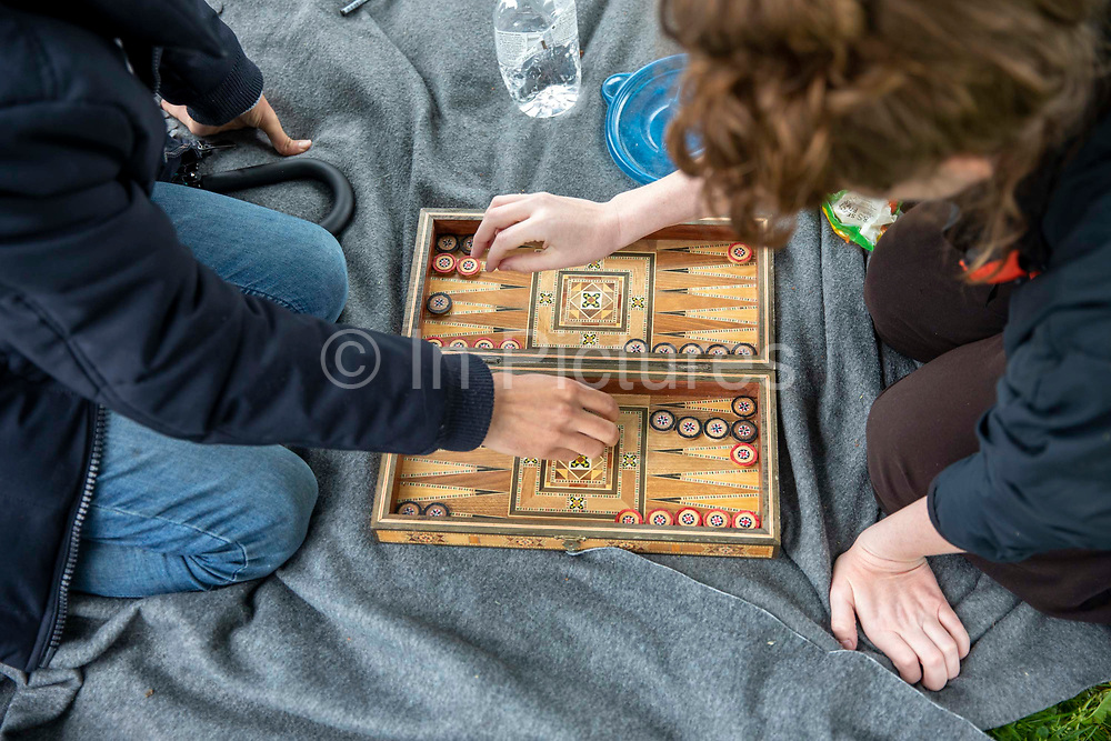 A residents of Napier Barracks playing backgammon with someone as 200 campaigners from different local groups came together today for a festival of solidarity with residents of Napier Barracks, a former military barracks that is being used as an assessment and dispersal facility for asylum seekers by the Home Office on the 21st of May 2021 in Folkestone, Kent, United Kingdom.