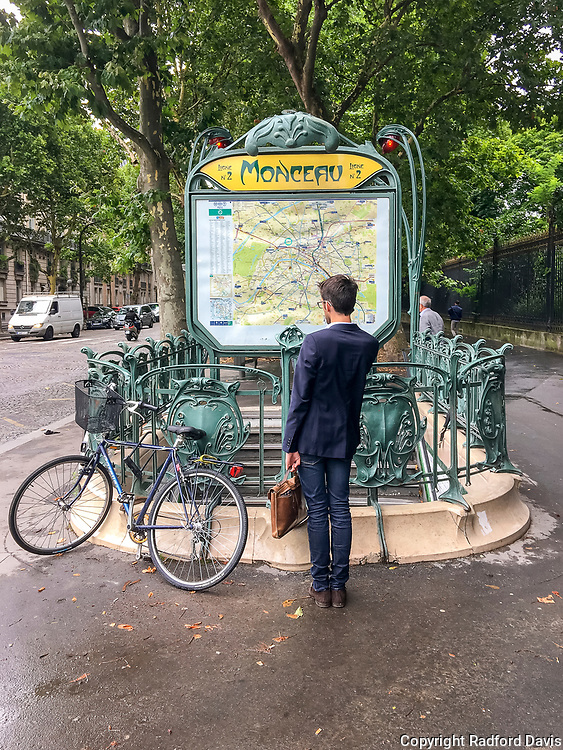 Man looks at a map near a metro station, Paris, France