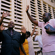 "Hundreds of Haitians pray at The Church of God, Rue de Centre 3, during the Sunday service ( 07/02/10) The church was damaged during the earthquake with  many  of the choir singers entombed. Sylvie Selde remembers ""The entire group of singers practising were killed. We are still recovering the bodies now, only nine so far. When we recover them we take them to the mass grave or dig a hole and put them in. This is a message from  God, a  judgement,  do the right thing. Stop being wicked"".  Many believe that in Port Au Prince one Haitian Alex K Juste is more positive ""That day, there was no rich, no poor, no colour, no prejudice, no racism. We were equal, they knew that God existed and their hands were up in the air praising the Lord. We held hands, we cared for each other, we supported the sick.  What a beautiful thing to see us Haitians reunited, together as one""."