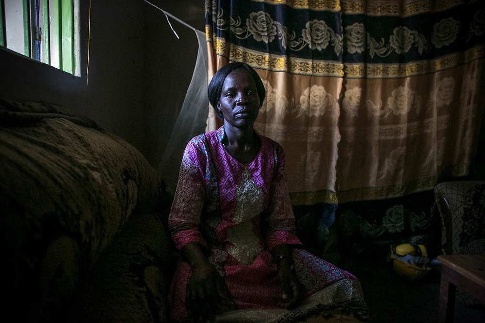 Acheng Irine, a former sex slave of LRA, sits in her home in Gulu. She was abducted by LRA forces in the middle of the night when she was about 13 years old at St. Mary's school and was assigned to a commander six months later. She became the 7th wife and gave birth to one daughter who is now 25 years old. She works as a building painter. Irine stayed in the bush for 9 or 10 years.