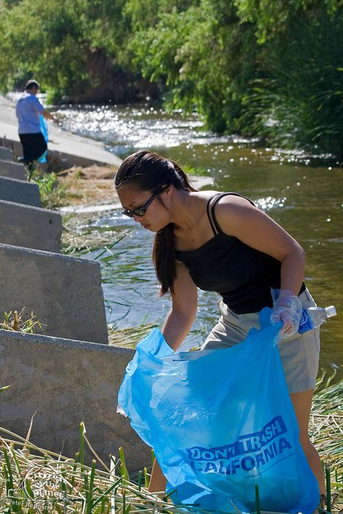 "Asian Women picking up trash in LA River. FoLAR's annual ""La Gran Limpieza"" clean up of the Los Angeles River. Bette Davis Picnic Area. Glendale Narrows. Los Angeles."