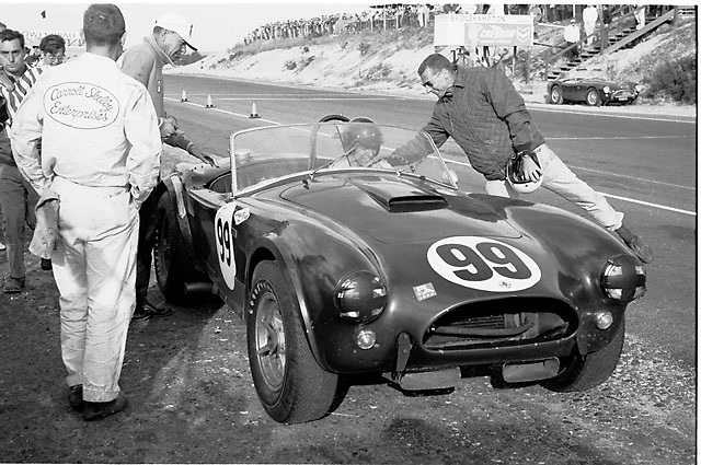 Carroll Shelby, in cap at left approaching car, and Dan Gurney at wheel of Shelby Cobra as fellow driver Bob Holbert moves in from right to congratulate Gurney for victory at Bridgehampton 1964