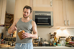 Man standing in kitchen and grinding coffee grinder, Munich, Bavaria, Germany