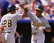"KANSAS CITY- 1989: Ricky Henderson of the Oakland Athletics gives ""the base"" to Stan Javier during an MLB game at Kaufmann Stadium in Kansas City, Missouri during the 1989 season. (Photo by Ron Vesely) Subject:   Rickey Henderson"
