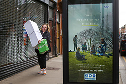 © Licensed to London News Pictures. 03/04/2021. London, UK. A woman walks past the government's 'Meeting up again? Stick to six.' latest advertising campaign poster in Haringey, north London as Covid-19 cases are rising in some London boroughs, including Haringey. Photo credit: Dinendra Haria/LNP