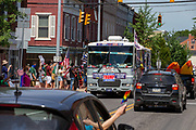 An RV covered in Trump signs drives through the Mifflinburg Pride Event.