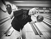 An elderly man poses for the camera before taking his turn in a game of bowling.