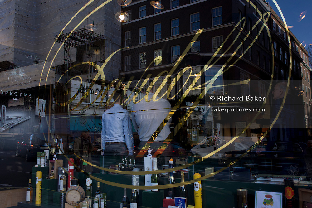 Two assistands await customers, seen through the window of cigar retailer Davidoff of London in stylish St. James's, London.