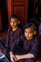 Young novice Buddhist monks with their heads partially shaved at the Thien Mu Pagoda (Pagoda of the Celestial Lady) is a historic temple in the city of Hue in Vietnam. Its iconic seven-storey pagoda is regarded as the unofficial symbol of the city. Hue, Central Vietnam.