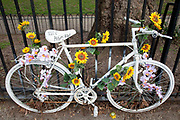 Ghost bike with fresh flowers in East London. A ghost bike or ghostcycle is a bicycle set up as a roadside memorial in a place where a cyclist has been killed or severely injured (usually by a motor vehicle). Apart from being a memorial, it is usually intended as a reminder to passing motorists to share the road. Ghost bikes are usually junk bicycles painted white, sometimes with a placard attached, and locked to a suitable object close to the scene of the accident. Many of these memorials are political statements erected by individuals who aim to make a wider point beyond personal loss regarding general road cyclist awareness.