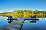 tourist sitting on bench admiring the view of a northern lake in the morning<br />Duck Mountain Provincial Park<br />Manitoba<br />Canada
