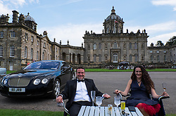© Licensed to London News Pictures.22/08/15<br /> Castle Howard, North Yorkshire, UK. <br /> <br /> JOHN and CATHERINE BENSON from Burythorpe enjoy a drink in front of their Bentley as hundreds of people attend the 25th anniversary of the Castle Howard Proms event near York. The theme of the event this year is a commemoration of the 75th anniversary of the Battle of Britain and the 70th anniversary of VE day and brings an evening of classic musical favourites celebrating Britishness to the lawns of Castle Howard.<br /> <br /> Photo credit : Ian Forsyth/LNP