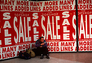 A young man rests in the front of a London branch of Topshop. Surrounded by Sale posters that hide the merchandise behind the glass, the man exhales the smoke from a cigarette with his bags alongside on the floor. The large red lettering attracts the attention of passing shoppers to this womens' fashion outfitters on Oxford Street. Topshop is a British multinational retailer which specialises in fashion clothing, shoes, make-up and accessories. It has around 440 shops across 33 countries and online operations in a number of its markets. It is part of the Arcadia Group, which is controlled by Philip Green and owns a number of other retail outlets including Burton, Dorothy Perkins and Miss Selfridge.