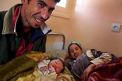 Aziz Bahassou, 26, holds his daughter for the first time while his wife Saida Ouchib, 26, rests moments after her birth in Ourika, Morocco on May 11, 2009. The couple came from their village to give birth with the help of the Dar el Oumouma maternity house.