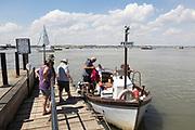 Passengers boarding River Deben foot passenger ferry boat at Bawdsey Quay, Suffolk, England, UK
