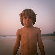 Child stands for a portrait at sunset.