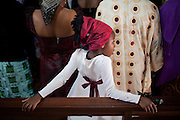 A girl is looking around while priest Norbert Gokum, 40, is celebrating a Mass Service at Saint Theresa's Christian Catholic Church in Jos, Plateau State, Nigeria. Saint Theresa's is the first Christian Catholic Church built in Jos, in 1923.