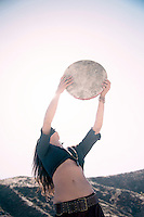 Beautiful wild woman playing a primitive drum. Earth Day Drummer