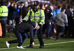 Fans on the pitch are confronted by police after the game
