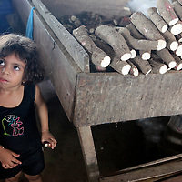 South America, Brazil, Manaus. Young girl watches over manioc, or cassava, in the market of Manaus.