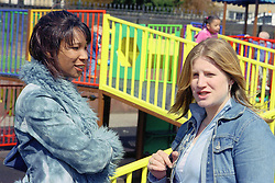 Two single mothers standing in playground talking,