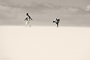 Nominated for 11th International B&W Spider Awards<br /> <br /> Just a simple observation of two people walking along the summit of a huge wind-blown sand-dune in Fuerteventura. The fashion seemed so incongruous to the situation, and I loved the human relationship in this vast space, between the second man bending forward as his companion strode ahead oblivious.
