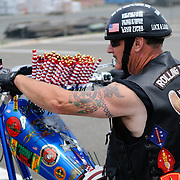 Vietnam Vet participating in the annual Rolling Thunder motorcycle rally through downtown Washington DC on May 29, 2011. This shot was taken as the riders were leaving the staging area in the Pentagon's north parking lot, where thousands of bikes and riders had gathered. The rider has dozens of small flags furled on his handlebars to give out along the route.