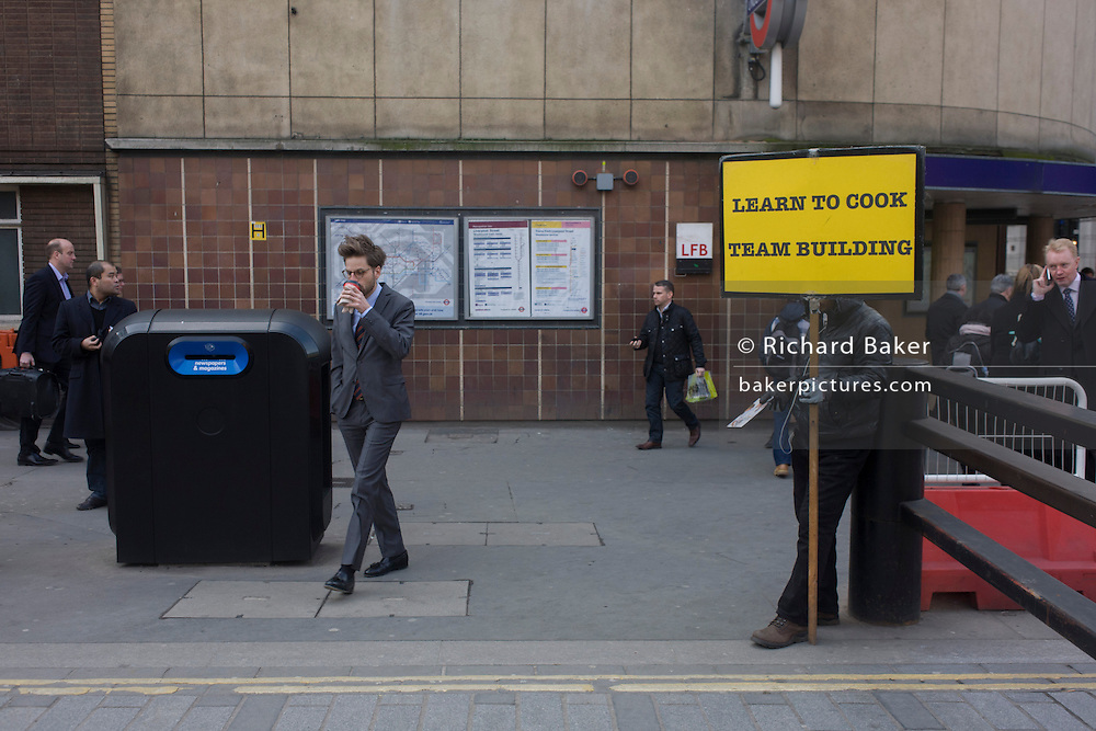 In Liverpool Street, London a man holds a sign promoting cookery lessons that leads to team building and teamwork,