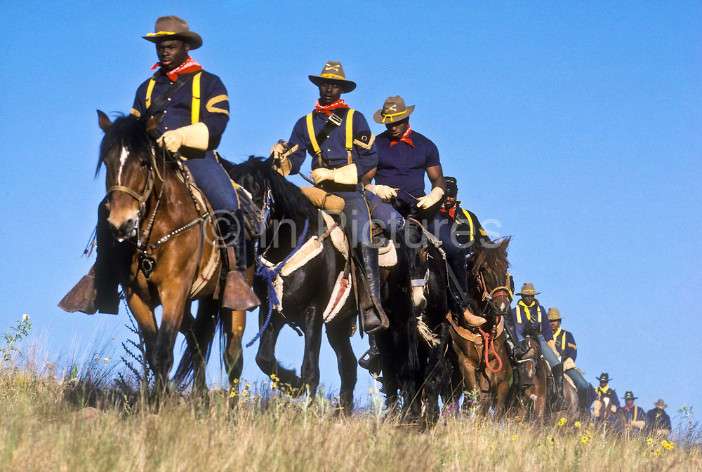 """A group of young juvenile (criminal)  offenders participate in an """"open prison"""" rehabilitation programme designed to build self esteem, courage, purposeful lives, seen here on horse back crossing a Nevada landscape. They are known as """"Buffalo soldiers"""" and use the same clothing as Gral Custer and his cavalry used in the American civil war. Most of  the offenders are black, USA. This programme runs by th e name of Vision Quest's Wagon Train."""