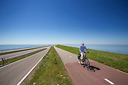 Fietsers rijden over de Afsluitdijk. In 1932 werd de opening tussen de Waddenzee (rechts) en de toenmalige Zuiderzee gesloten. Nu is het een belangrijke verkeersader tussen Friesland en Noord-Holland en scheidt het de Waddenzee met het IJsselmeer.<br /> <br /> Cyclists are riding on the Afsluitdijk. In 1932, the gap between the Wadden Sea and the former Zuiderzee closed by the Afsluitdijk. Now it is a major thoroughfare between Friesland and North Holland and it separates the Wadden Sea from the IJsselmeer.