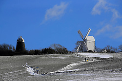 © Licensed to London News Pictures. 12/03/2013, Clayton, UK.  A man and a child walk up to snow covered Clayton Windmill, right, Clayton, West Sussex, England, as cold weather continues to affect much of UK, Tuesday, March 12, 2013. Photo credit : Sang Tan/LNP
