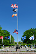 East Meadow, New York, USA. May 25, 2019. Flaying from a tall flagpole are, from top to bottom, the American Flag, the POW-MIA flag, and the Nassau County State of New York flag. It's surrounded by shorter flagpoles, each flying a military flag of the United States Armed Forces - Army, Navy, Marine Corps, Air Force, Coast Guard, at the Veterans Memorial Plaza at Eisenhower Park on Long Island.