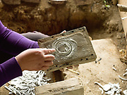Ms Vanthone, a metalworker prepares a wooden mould with ash to make bracelets from recycled aluminium sourced from Vietnam War debris and melted in an earthen kiln in Ban Naphia, a remote Tai Phouan village in mountainous Xieng Khouang Province in Northern Laos. Laos is the most bombed country, per capita, in the world with more than two million tons of ordnance dropped on it during the Vietnam War from 1963 to 1974. 12 artisan families began transforming war scrap into spoons (150,000 per year) in the 1970s to supplement subsistence farming activities. Supported by the Swiss NGO Helvetas, the project works to make the scrap metal supply chain safer for artisans and scrap collectors by collaborating with organisations such as Mines Advisory Group (MAG) that specialise in unexploded ordnance removal and education. More recently the villagers have started making bracelets and other items.