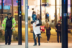 © Licensed to London News Pictures . FILE PICTURE DATED 23/05/2017 as Manchester prepares to mark a year since the Manchester Arena terror attack . Manchester, UK. Father ANDREW SENIOR carries his daughter EMILIA SENIOR away from the arena . Anxious parents wait by the police cordon for news of children inside the Manchester Arena . Police and other emergency services are seen near the Manchester Arena after Salman Abedi murdered 22 and injured dozens more at an Ariana Grande concert at Manchester Arena . Photo credit : Joel Goodman/LNP