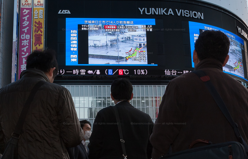 People watch news of the tsunami on large TV screens in Shinjuku after a magnitude .9 earthquake hit the Tohoku region of north east Japan causing tremors in Tokyo that stopped the train and cellphone networks. Many people were stranded in the centre of Tokyo over night. Tokyo, Japan Friday March 11th 2011