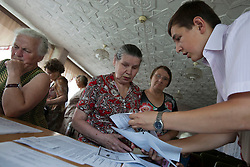 Ljudmila Datsjuk, left, is helped by a volunteer while attorney, Mykola Glotov, helps Nadia Zhuk, 70, during a Òspecial consultationÓ for potential clients who are children of the Second World War, RIvne, Ukraine, June 15, 2011. This vulnerable group is made up of seniors, most of whom are not receiving proper compensation as promised by the government. The legal team advises them on how to properly fill out forms and submit them to the courthouse, while encouraging them not to give up on their rights. More than half of the worldÕs population, four billion people, live outside the rule of law, with no effective title to property, access to courts or redress for official abuse. The Open Society Justice Initiative is involved in building capacity and developing pilot programs through the use of community-based advocates and paralegals in Sierra Leone, Ukraine and Indonesia. The pilot programs, which combine education with grassroots tools to provide concrete solutions to instances of injustice, help give poor people some measure of control over their lives.