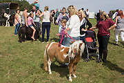 Young travellers try out Shetland ponies at the ancient annual Priddy Sheep (and horse) fair in Somerset, England. Set in the Mendip Hills, in the south-western English county of Somerset, the Priddy Sheep fair is host to an odd mix of farmers and travellers (commonly and incorrectly known as gypsies). In this field set aside purely for travellers, many with West Country accents but also with nearby Welsh and Irish too, deals are done with a traditional spit on the hand and a smacking of palms, selling a pony to another family. The Priddy Sheep Fair moved from the city of Wells in 1348 because of the Black Death.