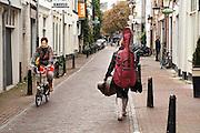 Een vrouw loopt met instrumenten in koffers door de Loeff Berchmakerstraat in Utrecht, terwijl een andere vrouw op een vouwfiets voorbij komt.<br /> <br /> A woman with all kinds of instruments is passing a cyclist on a folding bike at the Loeff Berchmakerstraat in Utrecht.