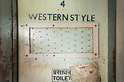 The Western Style toilet door entrance. Peeling paint frames the entrance to the toilets on the Vivek Express–one of the less glamorous parts of the journey. Inside the Dibrugarh-Kanyakumari Vivek Express, the longest train route in the Indian Subcontinent. It joins Kanyakumari, Tamil Nadu, which is the southernmost tip of mainland India to Dibrugarh in Assam province, near the border with Burma.