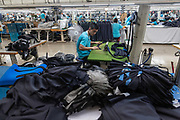 Employees make suits at a factory operated by the Shandong Ruyi Technology Group in Jining, China, on Monday, May 30, 2016. Shandong got a boost in the past from its proximity to Japan and South Korea, the source of much of its early investment. Now, its trying to maintain the high growth rate needed to make the same leap they did: from middle- to high-income status.